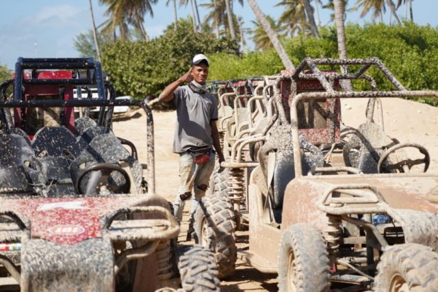 Man smiles near muddy offroad vehicles